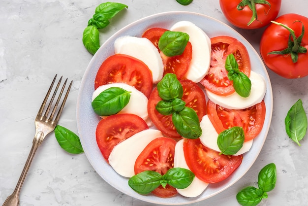 Fresh italian caprese salad with sliced tomatoes, mozzarella cheese, basil, olive oil and fork in a plate