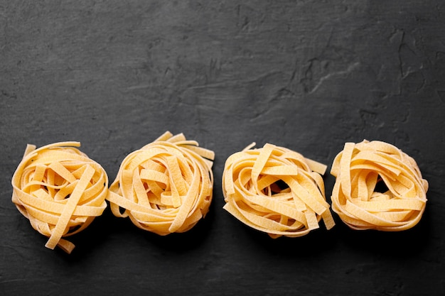 Fresh italian pasta l on a dark background with copy space for text. tagliatelle pasta nests.