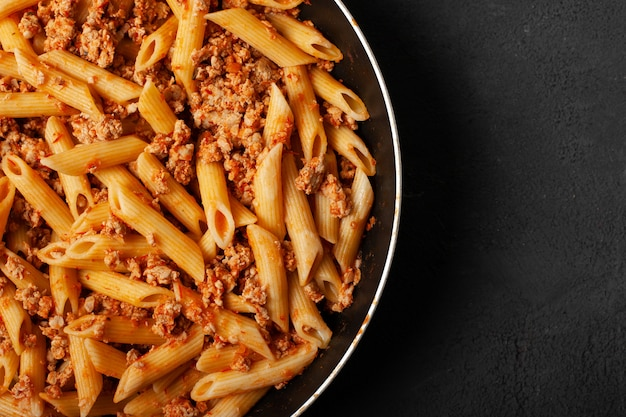 Fresh italian penne pasta bolognese on frying pan and dark concrete background top view with copy space.