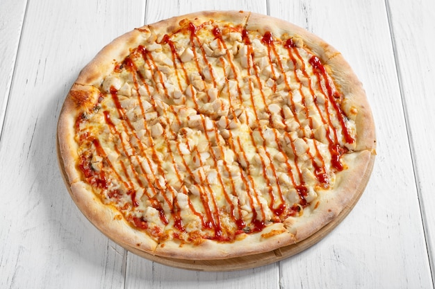 Fresh italian pizza with chicken on wooden table
