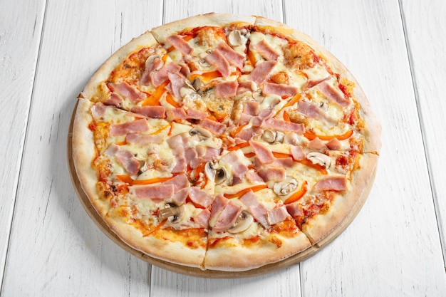 Fresh italian pizza with ham and mushrooms on white wooden table