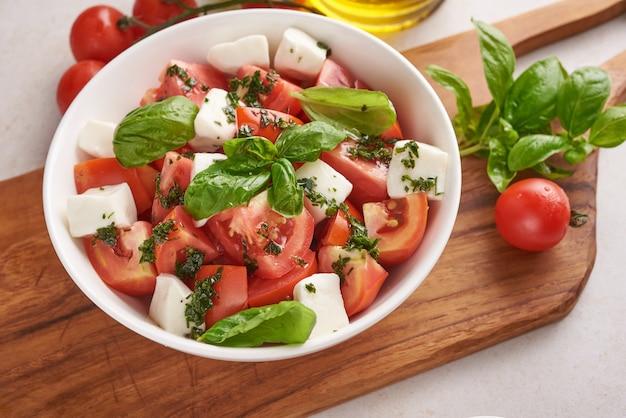 カプレーゼと呼ばれる新鮮なイタリアンサラダの前菜、バッファローモッツァレラチーズ、スライストマト、バジルとオリーブオイル。ベジタリアンカプレーゼサラダの材料。イタリア料理。上面図。素朴なスタイル。
