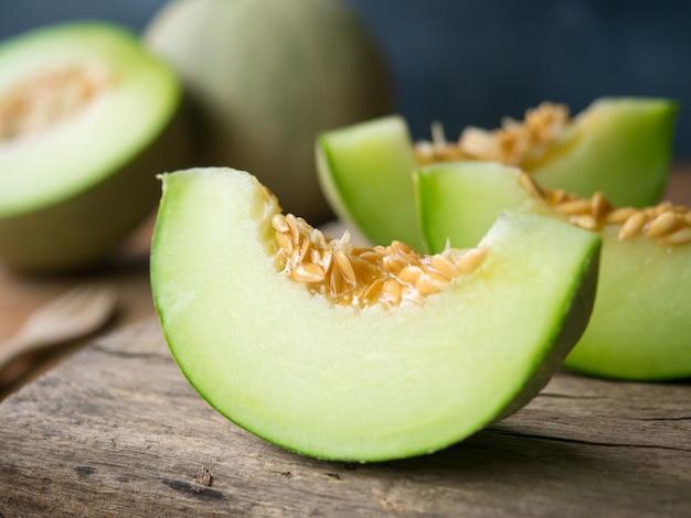 나무 테이블에 얇게 썬 신선한 일본 녹색 멜론 과일.