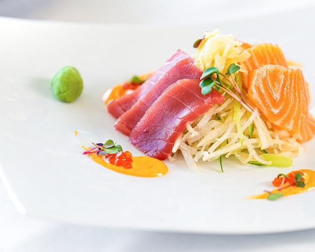 Ломтик свежей японской сырой рыбы сашими на тарелке