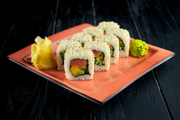 Свежие японские суши-роллы с авокадо, огурцом и лососем, поданные на тарелке с васаби и имбирем на темном фоне.