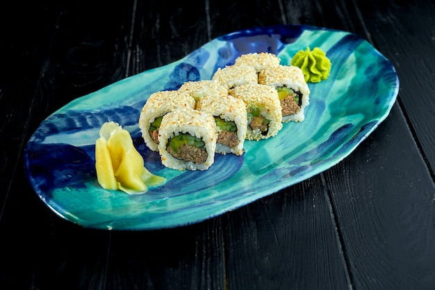 """アボカド、キュウリ、ðµð³ñ'ñ""""を添えた新鮮な日本の巻き寿司を、暗い背景にわさびと生姜を添えた皿に盛り付けます"""