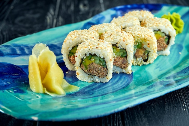 Fresh, japanese sushi rolls with avocado, cucumber and ????, served in a plate with wasabi and ginger on a dark surface. japanese kitchen. california roll in sesame