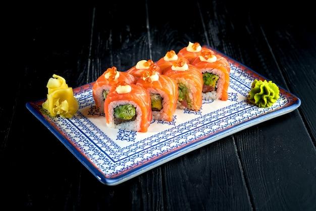 きゅうり、キャビア、サーモンを添えた新鮮な日本の巻き寿司を、暗い背景にわさびと生姜を添えた皿に盛り付けました。日本のキッチン。ゴマの赤いドラゴンロール