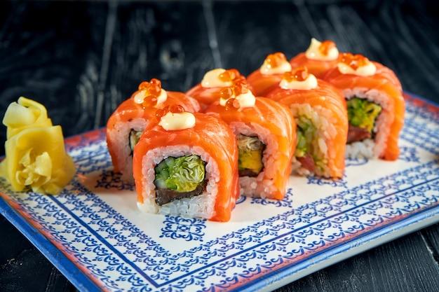 Свежие японские суши-роллы с огурцом, икрой и лососем, подаются на тарелке с васаби и имбирем на темной поверхности. японская кухня. ролл красный дракон в кунжуте