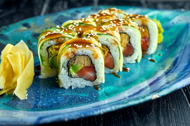 Fresh, japanese sushi rolls with cucumber, unagi sauce and salmon, served in a blue plate on a dark surface. japanese cuisine