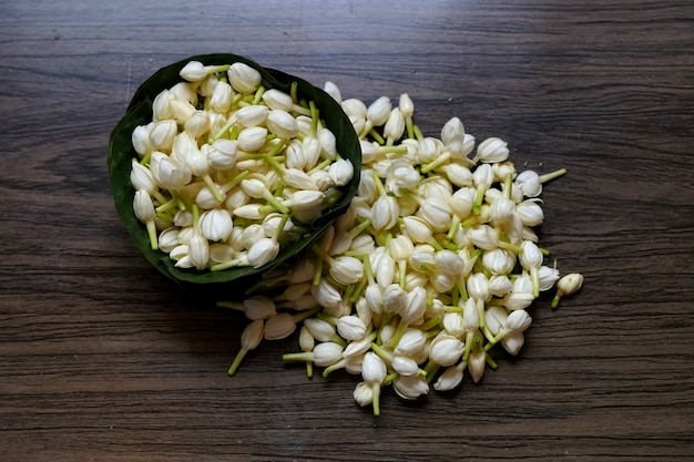 Fresh jasmine flowers in banana leaves bowl on wooden table for water spa