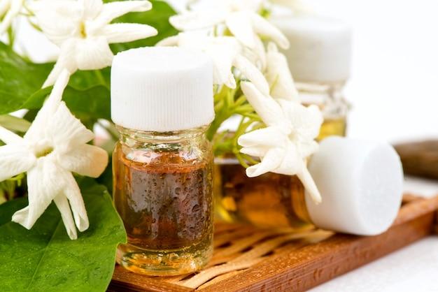 Fresh jasmine flowers and perfume isolated on white .
