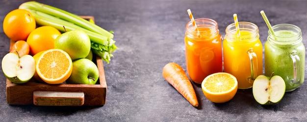 어두운 테이블에 과일과 야채와 신선한 주스와 스무디