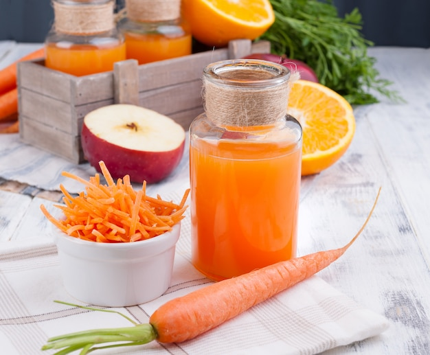 Fresh juice of carrot, apple, orange and lemon. carrots with leaves and other fresh fruits on a white wooden background
