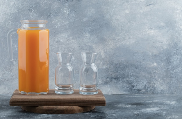 Fresh juice and empty glasses on wooden board.