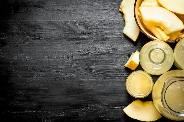 Свежий сок из спелых дынь в кувшине и стаканах. на черном деревянном столе.