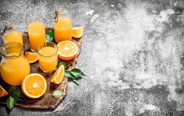 素朴な背景に熟したオレンジからのフレッシュジュース