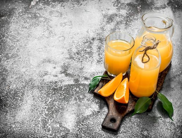 熟したオレンジからのフレッシュジュース。素朴な背景に。