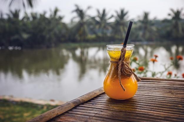 코코넛 나무의 배경에 아름 다운 유리에 노란색 열 대 과일에서 신선한 주스.