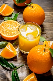 Fresh juice in glass and oranges slices with leaves