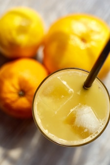 Fresh juice in a glass with ice on the table and oranges