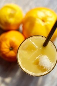 Свежевыжатый сок в стакане со льдом на столе и апельсинами