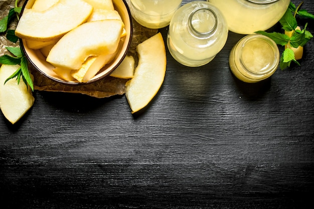 Свежий сок дыни с ветками свежей мяты. на черном деревянном столе.