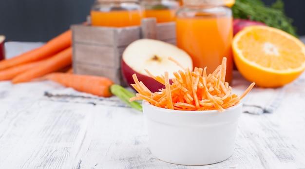 당근, 사과, 오렌지, 레몬의 신선한 주스. 나뭇잎과 흰색 나무 배경에 다른 신선한 과일과 당근