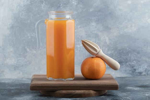Succo fresco e arancia con alesatore su tavola di legno.