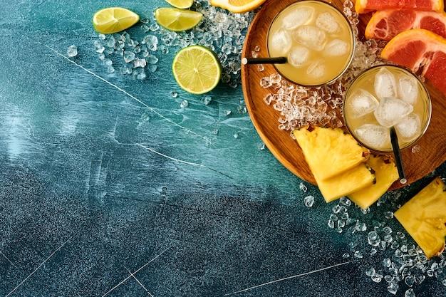 얼음과 다양 한 신선한 주스 파인애플 슬라이스 익은 색 열 대 과일 자 몽, 오렌지, 라임, 레몬, 평면 누워 구성, 진한 파란색 돌 배경.