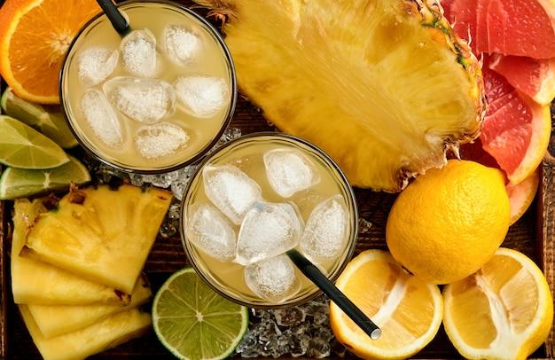 ダークブルーの石の表面に、色のトロピカル フルーツ グレープ フルーツ、オレンジ、ライム、レモン、フラット レイの構成を熟した氷とさまざまなスライスしたフレッシュ ジュース パイナップル。