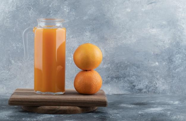 Succo di frutta fresco e due arance su tavola di legno.