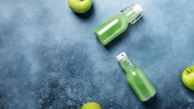 青いテーブルの上の緑のリンゴとフレッシュジュース