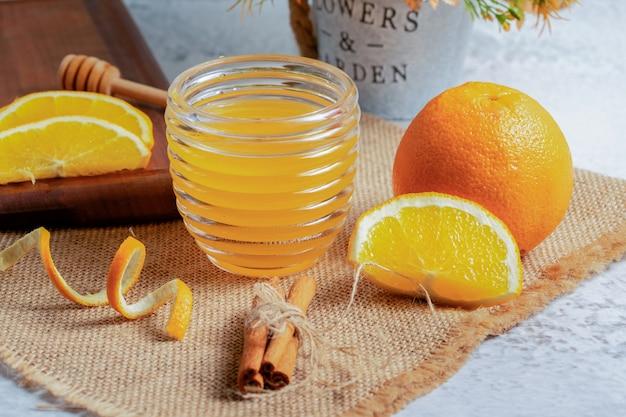 회색 벽에 오렌지 조각과 신선한 주스입니다.