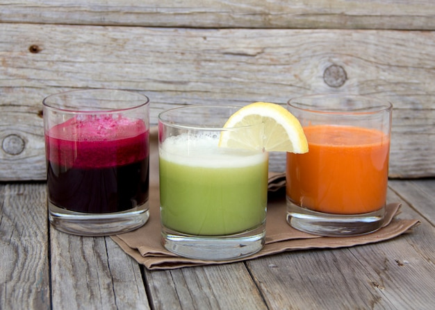 Fresh  juices - red beet, cabbage and carrot on a wooden table close up