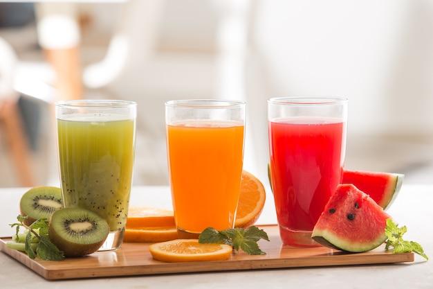 신선한 주스 스무디 세 유리 빨강 녹색 오렌지 열대