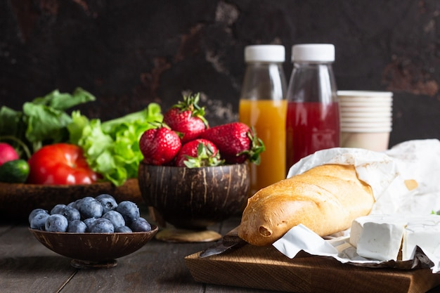 Fresh juices, various vegetables and berries, baguette and cheese