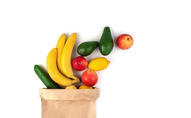 Свежие, сочные бананы, авокадо, яблоки и лимоны изолированы на белом фоне.