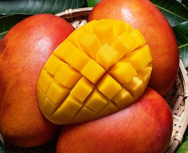 Свежие сочные красивые нарезанные кубиками плоды манго в бамбуковой корзине на зеленых листьях