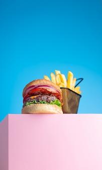 신선한 육즙 쇠고기 햄버거와 튀긴 감자 튀김은 분홍색 스탠드와 파란색 배경에 배치됩니다. 텍스트, 트렌디 한 영웅보기를위한 공간 복사