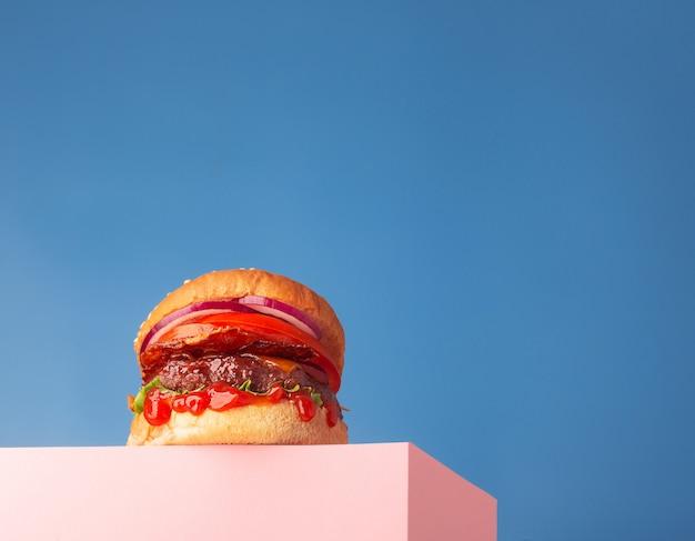 ピンクのスタンドと青い背景に置かれた新鮮なジューシーな牛肉のハンバーガー。テキスト、トレンディなヒーロービュー、水平方向のコピースペース