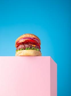 ピンクのスタンドと青い背景に置かれた新鮮なジューシーな牛肉のハンバーガー。テキスト、トレンディなヒーロービューのコピースペース