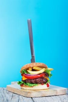 青の創造的なトレンディな背景に置かれたフライドポテトとナイフで新鮮なジューシーな牛肉のハンバーガー