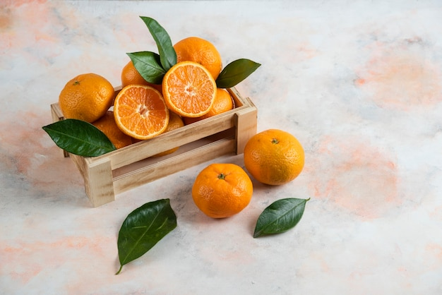 Fresh juicy clementine in wooden box. whole or half cut