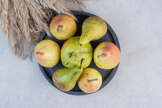黒いプレートに新鮮なジューシーなカラフルな梨。