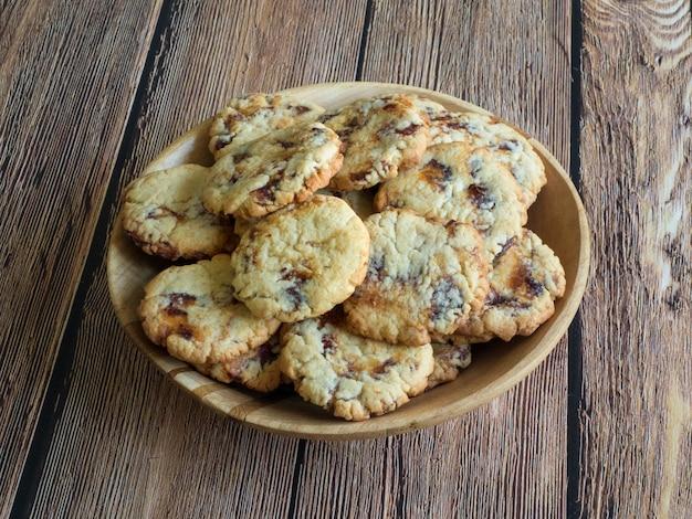 茶色の木の表面にボウルにジューシーな日付の新鮮なクッキー