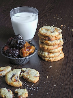 Fresh juicy date cookies with milk on a dark wooden surface