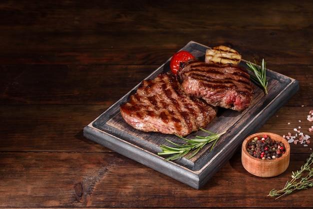 어두운 배경에 신선한 육즙 맛있는 쇠고기 스테이크. 향신료와 허브와 고기 요리