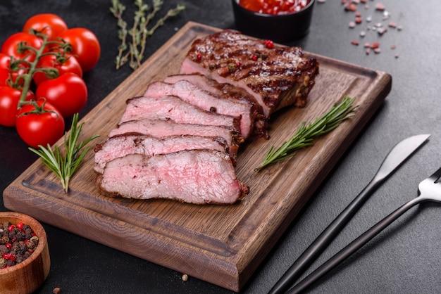 Свежий сочный вкусный стейк из говядины на темном фоне. мясное блюдо со специями и зеленью