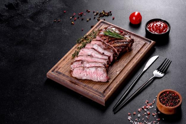 어두운 표면에 신선한 육즙 맛있는 쇠고기 스테이크. 향신료와 허브와 고기 요리